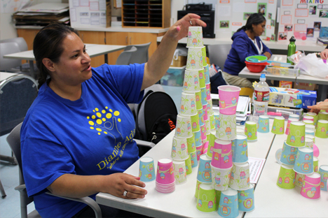 Student instructor builds a tower with several small paper cups.