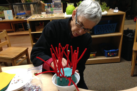 Student instructor uses pipe cleaners and paper cups to construct a creative art piece.